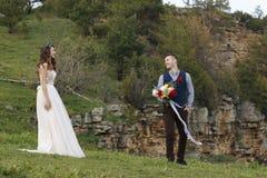 在婚礼的夫妇盛装与花花束,并且绿叶在手里反对领域的背景在 库存照片