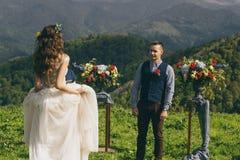 在婚礼的夫妇盛装与花花束,并且绿叶在手里反对领域的背景在 免版税图库摄影