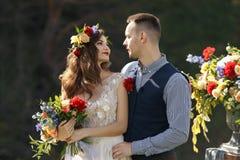 在婚礼的夫妇盛装与花花束,并且绿叶在手里反对领域的背景在 图库摄影