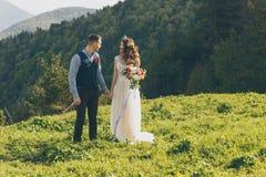 在婚礼的夫妇盛装与花花束,并且绿叶在手里反对领域的背景在 免版税库存图片