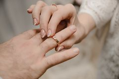 在婚礼的年轻夫妇交换圆环 免版税图库摄影