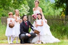 在婚礼的新娘夫妇与孩子 免版税库存照片