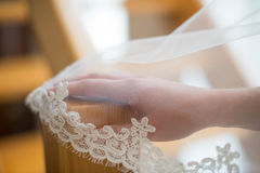 在婚礼的新娘的手在面纱下 免版税库存照片