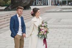 在婚礼礼服和衣服的结婚的爱恋的夫妇 愉快新娘和新郎走的跑在夏天城市 免版税库存图片