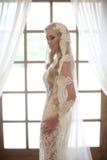 在婚礼礼服的美丽的新娘画象与长的新娘面纱 图库摄影
