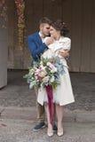 在婚礼礼服的结婚的爱恋的夫妇和衣服室外在城市设置对墙壁 愉快新娘和新郎笑 免版税库存照片