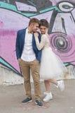 在婚礼礼服的结婚的爱恋的行家夫妇和衣服室外在城市设置对五颜六色的街道画墙壁 库存图片