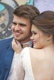 在婚礼礼服的结婚的爱恋的行家夫妇和衣服室外在城市设置对五颜六色的街道画墙壁 库存照片