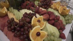 在婚礼自助餐桌上的不同的新鲜水果 婚姻桌装饰的果子和莓果 自助餐招待会果子 股票录像