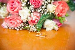 在婚礼花束新娘的背景的婚戒 库存图片