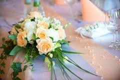 在婚礼餐桌上的花花束 免版税库存照片