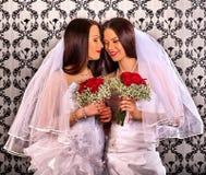 在婚姻新娘礼服亲吻的女同性恋的夫妇 库存照片