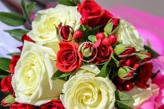 在婚姻花束的玫瑰的金戒指 库存图片