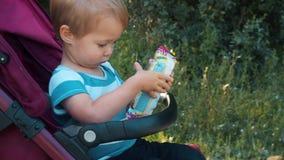 在婴儿推车的高兴的孩子骑马 股票录像