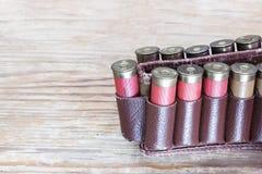 在子弹带的老狩猎弹药筒在一张木桌上 库存图片