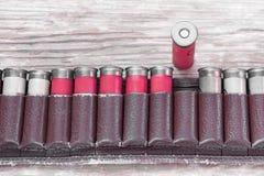 在子弹带的老狩猎弹药筒在一张木桌上 免版税库存照片