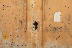 在子弹的一个十字架钻孔了墙壁,黎巴嫩 免版税库存照片