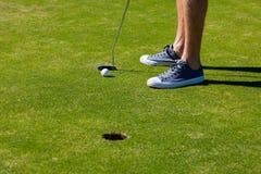 在孔旁边的男性高尔夫球运动员脚 免版税库存照片