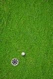 在孔的球在高尔夫球场 免版税库存照片