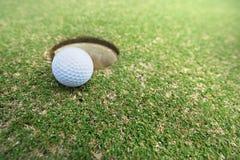 在孔的球在高尔夫球场 免版税图库摄影