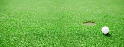 在孔的边缘的高尔夫球 库存照片