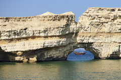 在孔的阿拉伯单桅三角帆船在岩石 库存图片