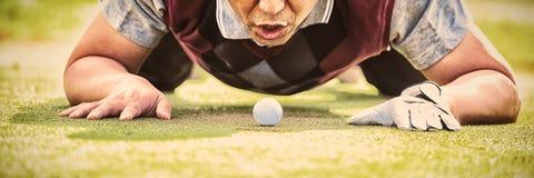 在孔的高尔夫球运动员吹的球 库存图片