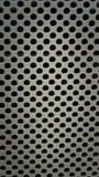 在孔纹理背景中刺穿的金属板材 免版税图库摄影