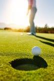 在孔边缘的高尔夫球与球员的在背景 免版税库存照片