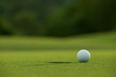 在孔附近的白色高尔夫球在航路有绿色背景我 免版税库存图片
