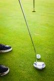 在孔附近的高尔夫球运动员 免版税图库摄影