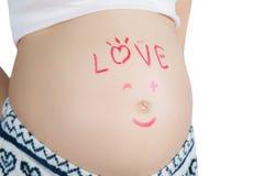 在孕妇的腹部的红色smilies 库存图片