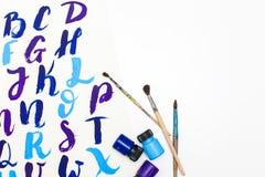 在字母表上写字的书法得出与干燥刷子 英国ABC信写与画笔 库存图片