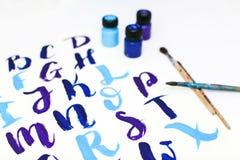 在字母表上写字的书法得出与干燥刷子 英国ABC信写与画笔 免版税图库摄影