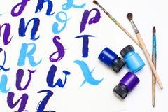 在字母表上写字的书法得出与干燥刷子 英国ABC信写与画笔 免版税库存图片