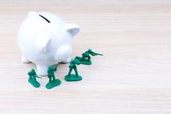 在存钱罐前面的绿色小锡兵 免版税库存照片