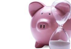 在存钱罐旁边怂恿定时器,白色的 库存图片