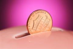 在存钱罐的便士 免版税库存照片