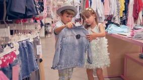 在季节性折扣期间,购物假日,小朋友选择新的时髦的服装在商店 股票视频