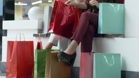 在季节性期间,Shopaholism,考虑购买的女朋友入包裹在时兴的鞋子的腿附近关闭  股票视频