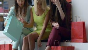 在季节性销售期间,折扣的季节,考虑购物的公司妇女入袋子在生动的鞋子的腿附近关闭  股票录像