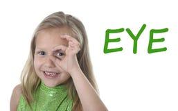 在学会英国词的身体局部的逗人喜爱的小女孩盘旋的眼睛在学校 免版税库存照片