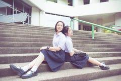 在学校倾斜的逗人喜爱的亚洲泰国高女小学生学生夫妇 免版税库存图片