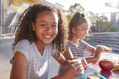 在学校午餐桌,一上微笑对照相机的女朋友 免版税图库摄影