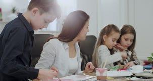 在学校母亲以后的一个大宽敞客厅有她的做从家庭作业的三个孩子的一个学校项目非常 影视素材