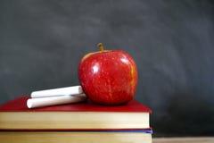 在学校课本的红色苹果 库存图片