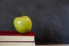 在学校课本的绿色苹果 库存照片