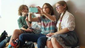 在学校走廊的智能手机的照相机拍摄的少年在断裂期间 有公文包的孩子坐 影视素材