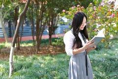 在学校阅读书的愉快的亚洲中国俏丽的女孩穿戴学生衣服在一棵树下本质上在春天 库存图片