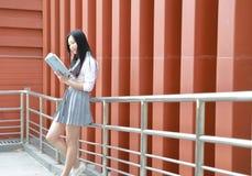 在学校阅读书的愉快的亚洲中国俏丽的女孩穿戴学生衣服本质上在春天 免版税图库摄影